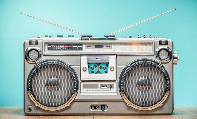 Retro outdated portable stereo boombox radio receiver with cassette recorder from circa late 70s front aquamarine wall background. Listening music concept. Vintage old style filtered photo